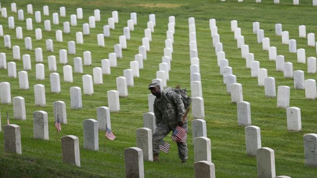 Members of the 3rd U.S. Infantry Regiment place American flags at the graves of U.S. soldiers buried at Arlington National Cemetery, in preparation for Memorial Day, in Arlington, Va., May 21, 2015. Getty Images